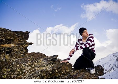 Junger Mann posiert in großer Höhe nach dem Aufstieg von einer Klippe