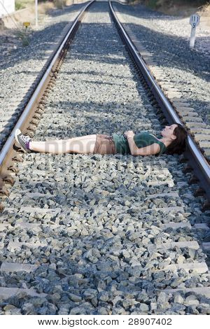 Young woman laying on a railway.