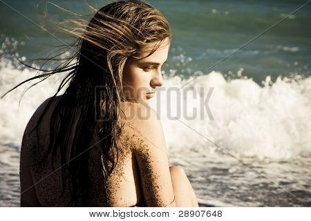 Frau fürsorglich in der Strand mit Sand in ihrer Haut.