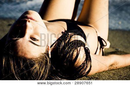 Laying green eyed beauty wearing black small bikini.