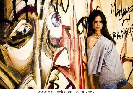 Young gothic woman on grafted urban wall