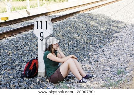 Young female backpacker near railroad