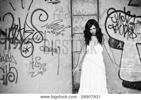 Elegant young woman in dirty location, black and white toned.