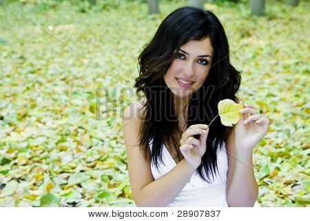 Beautiful smiling woman surrounded by fallen leaves