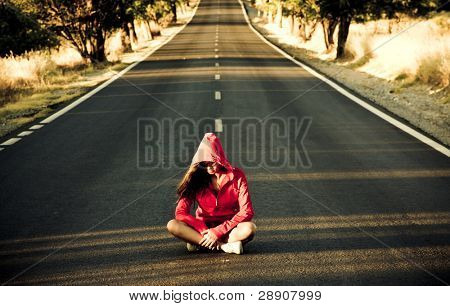 Unrecognizable mystery woman in the middle of the road.