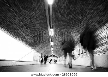 Blurred people on tunnel, black and white.