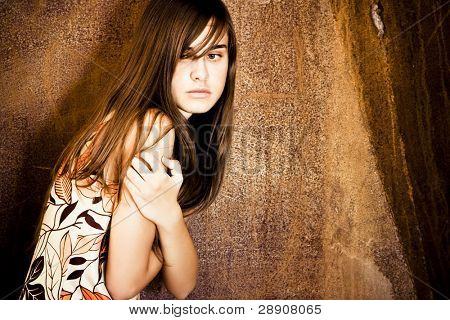 Young scared woman over grunge background