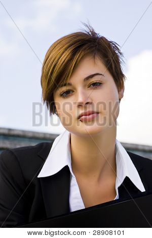 Short haired businesswoman over blue sky.