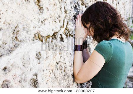 Joven mujer oración contra el muro de piedra.