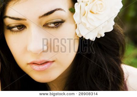 Hermosa joven con una rosa blanca en el pelo.
