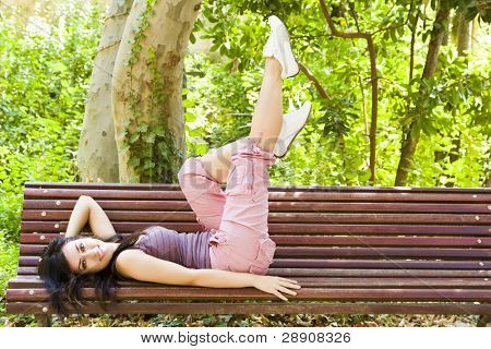 Young beautiful woman laying in a park bench