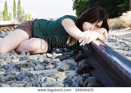 Sad young woman laying on the railway.