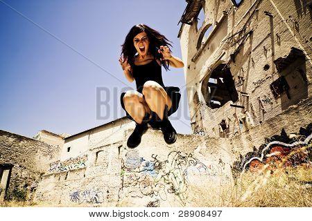Young woman jumping among ruins