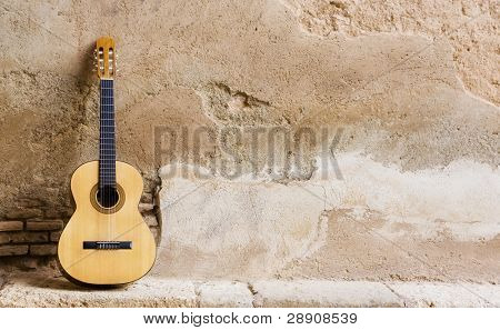 Spanish guitar on old wall, copy spaced.