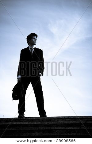 Silhouetted businessman posing on stairs against blue sky.