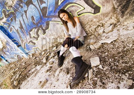 Rebel young girl sat in a dirty place.