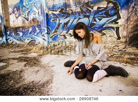 Rebel young girl sitting in a dirty place.