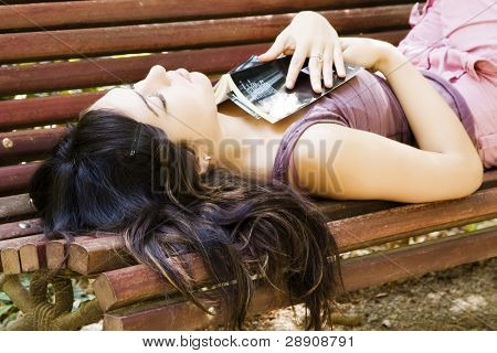 Young woman sleeping in a bench after reading a bool.