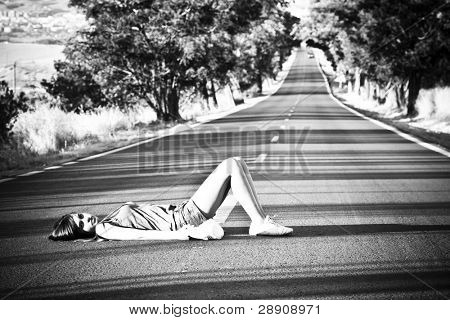 Young girl laying in the middle of nowhere.