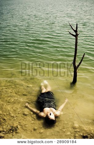 Young woman body over lake waters, closed eyes.