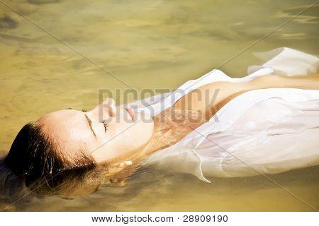 Sensual woman in water wearing white shirt