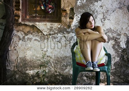 Young sad woman sited on dirty place.