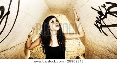 Terrified young woman inside of dirty place.