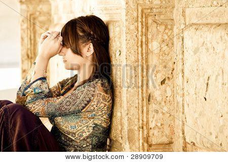 Junge besorgt Frau gegen alte Steinmauer