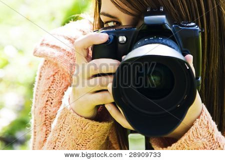 Young woman eye behind slr camera.