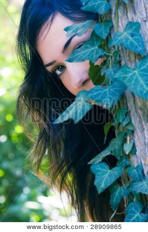 Young beautiful woman observing behind leaves.