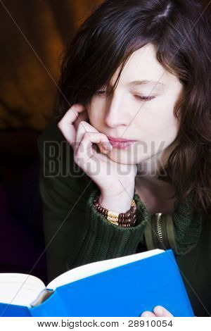 Young woman portrait reading a book.