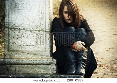 Sad woman sitting in a grave.