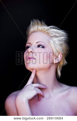 Young beautiful pensive blonde isolated on black