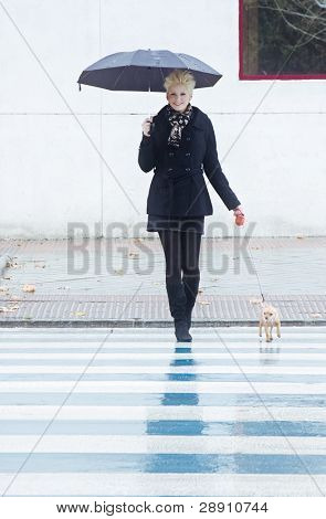 Young blond woman walking with her pet under rain.