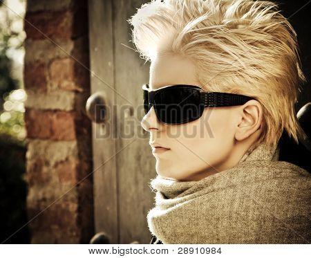 Joven mujer rubia en usar gafas de sol de moda de invierno.