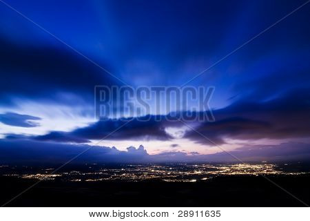 City lights on sunset under long exposed clouds