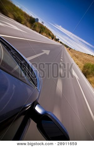 Cruising the countryside in a blue car at high speed.