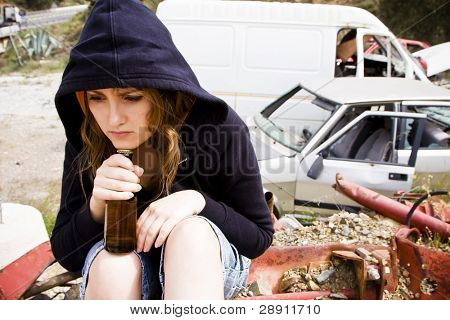 Young woman taking beer in the scrapyard