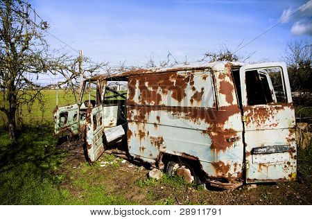 Rusty abandoned van in green field.
