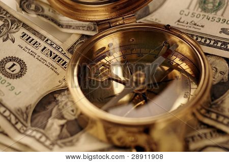 Navigating Financial Waters - An old brass compass over US currency