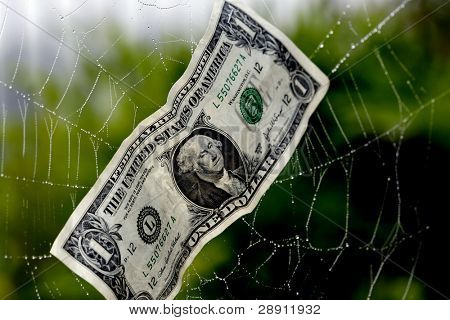 Caught In A Financial Web - a dollar bill in a spider web portrays the concept of being caught financially.