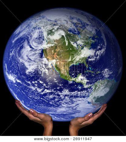 Manos sosteniendo la tierra. Tierra imagen cortesía NASA vía imágenes de dominio público.