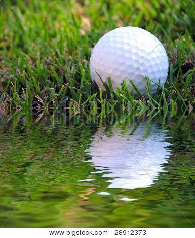 Difficult Shot! A golf ball in the rough and very close to a water hazard.