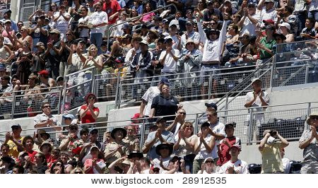 Large Crowd of People yelling and applauding at a baseball game.