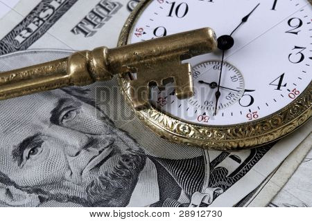 Time And Money Concept - skeleton key and old pocket-watch atop US currency.