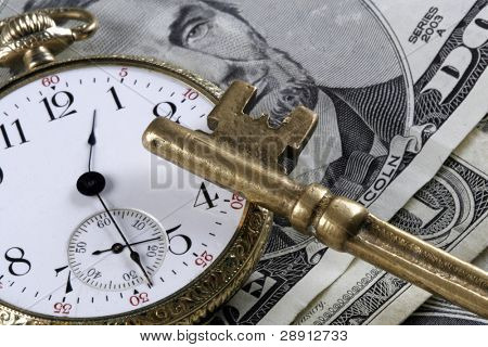 Time And Money Concept - skeleton key and old pocket-watch over US Currency