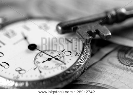 Time and money portrayal by skeleton key and watch. Tight focus on end of key. Black and white.
