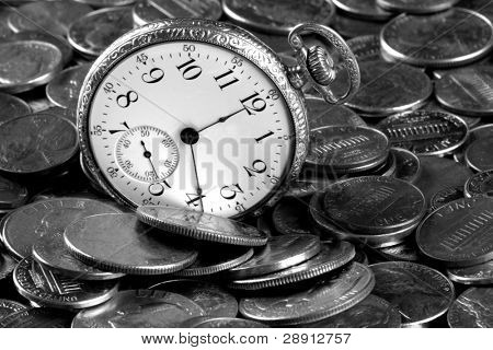 Time and money concept. US coins and an old pocket-watch. Image is black and white.