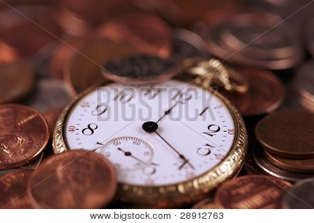 Time and money concept. US coins and an old pocket-watch.