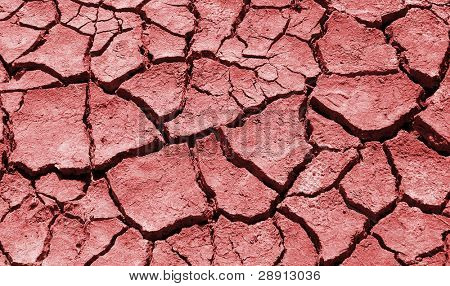 Cracked and dry red clay. A drought in the desert heat.